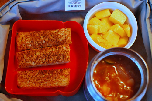 Homemade vegetable soup, cold grilled cheese sandwich strips for dipping, and frozen mango cubes.