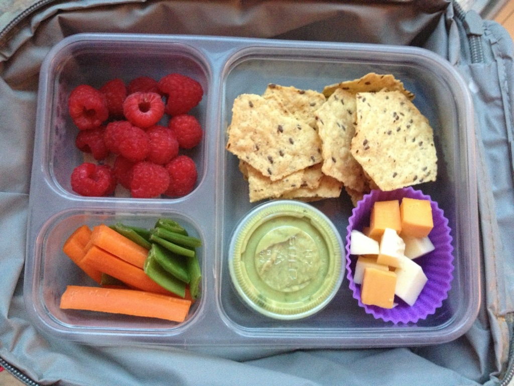 Food Should Taste Good Multi-grain Chips, guacamole, cheese cubes, carrots and snap peas, raspberries.