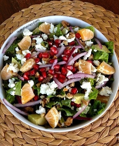 Salad with pomegranates, red onion, goat cheese, toasted walnuts, clementine, and avocado